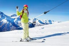 在按钮上去的滑雪电缆车的女孩上升,挥动的手 库存照片