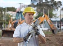 在挖掘机前面的建筑工人 免版税库存图片