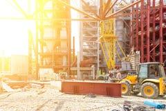 在挖掘机的工作者装配在一种工业设施的建筑 免版税库存照片