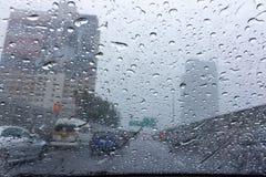 在挡风玻璃的雨下落 免版税库存照片