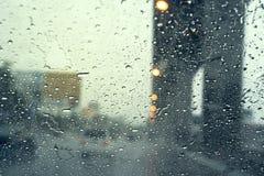 在挡风玻璃的雨珠,驾驶在路在镭的城市 库存照片