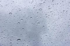 在挡风玻璃,背景的雨下落 免版税库存照片