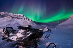 在挪威斯瓦尔巴特群岛朗伊尔城市snowscooter山的极性北极北极光极光borealis天空星 库存照片