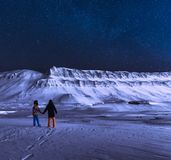 在挪威斯瓦尔巴特群岛朗伊尔城市snowscooter山的极性北极北极光极光borealis天空星 免版税库存图片
