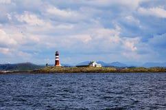 在挪威海岛上的灯塔在多云天 免版税库存照片