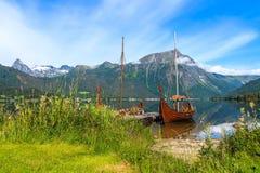 在挪威风景的老北欧海盗小船复制品 库存图片