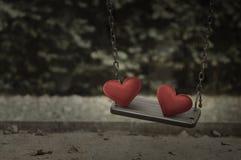 在损伤金属操场摇摆的织品红色心脏 免版税库存照片