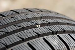 在损坏的轮胎的铁螺丝 库存图片
