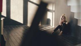 在损失铸件坐地板在舞蹈演播室户内后,年轻十几岁的女孩舞蹈家遭受 库存照片