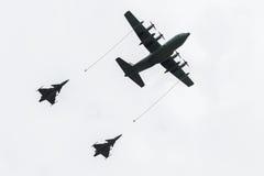 在换装燃料期间的航空器罐车两台喷气式歼击机。 免版税图库摄影