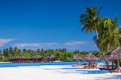 在掌上型计算机含沙结构树热带别墅的海滩 免版税库存照片