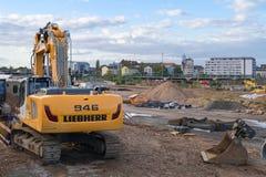 在掘土工期间的建造场所与在前景的一种新的挖掘机一起使用 海得尔堡,德国- 2017年10月3日 免版税库存图片