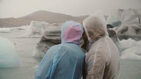 在探索著名视域的雨衣的年轻夫妇-在冰岛冰盐水湖 旅游人展示某事对妇女 股票视频