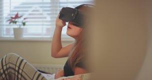 在探索虚拟现实玻璃的一个虚拟世界和发明的一个逗人喜爱的相当少年室女孩,非常 股票录像