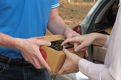 在接受包裹的巧妙的电话的妇女签署的署名从d 免版税图库摄影