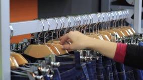在接触的女性手与衣裳的一支挂衣架在精品店 影视素材