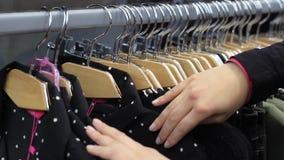在接触的女性手与衣裳的一支挂衣架在精品店 股票录像