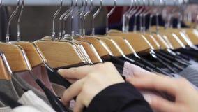 在接触的女性手与衣裳的一支挂衣架在精品店 股票视频