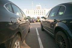 在接近彼此的城市停放的两辆汽车 免版税库存照片