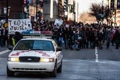 在控制交通的抗议者前面的警车 库存照片
