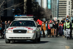 在控制交通的抗议者前面的警车 库存图片