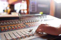 在控制音量控制器的男性手在控制台 有工程师或音乐生产商的录音演播室混合的书桌 免版税图库摄影