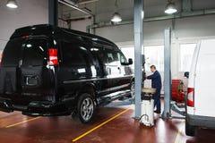 在推力的技工上升的汽车在维护前 免版税库存图片