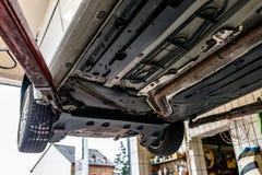 在推力的汽车底盘,从底部的看法 可看见的排气系统,轮子,闸水管 免版税库存照片