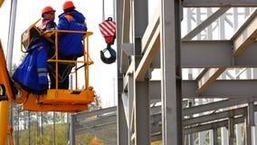 在推力的起重机提起两名工作者 影视素材