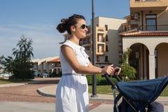 在推挤摇篮车(婴儿车)的城市街道上的现代母亲 免版税库存照片
