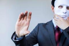 在掩藏的面具的匿名商人有举行某事姿态-与copyspace 库存图片