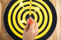 在掷镖的圆靶的中心的红色箭箭头 免版税库存照片