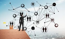 在提出网络和连接概念的房子屋顶的商人 混合画法 库存图片