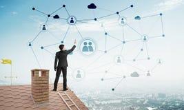 在提出网络和连接概念的房子屋顶的商人 混合画法 库存照片