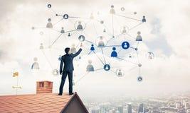 在提出网络和连接c的房子屋顶的商人 库存图片