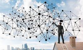 在提出网络和连接概念的房子屋顶的商人 混合画法 免版税库存图片