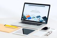在提出iOS 8的书桌上的苹果计算机设备 库存照片