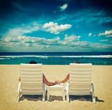 在握手的海滩睡椅的夫妇临近海洋 图库摄影