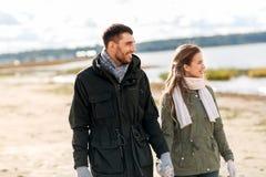 在握手的秋天海滩的愉快的夫妇 库存图片