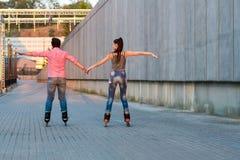 在握手的直排轮式溜冰鞋的夫妇 免版税图库摄影