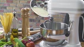 在搅拌器的贝克倾吐的面粉粉末揉的面团的在面包店 烹调在厨房机器的倾吐的面粉混合的面团的 股票视频