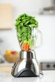在搅拌器的绿色菜圆滑的人 免版税库存图片