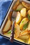 在搪瓷烘烤盘的被烘烤的土豆楔子 免版税库存图片