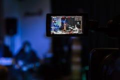 在摄象机的LCD显示 音乐会的摄制 播放低音提琴、合成器、吉他和撞击声的音乐家 库存图片