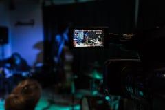 在摄象机的LCD显示 音乐会的摄制 播放低音提琴、合成器、吉他和撞击声的音乐家 免版税库存照片