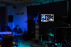 在摄象机的LCD显示 音乐会的摄制 播放低音提琴、合成器、吉他和撞击声的音乐家 图库摄影