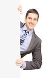 在摆在一个备用面板后的衣服的年轻商人 图库摄影