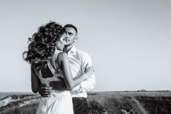 在摆在与完善的天空的日落的领域、恋人或者新婚佳偶的美好的夫妇 黑色白色 免版税库存照片