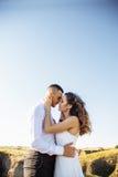 在摆在与完善的天空的日落的领域、恋人或者新婚佳偶的美好的夫妇 库存照片