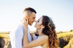 在摆在与完善的天空的日落的领域、恋人或者新婚佳偶的美好的夫妇 免版税库存图片